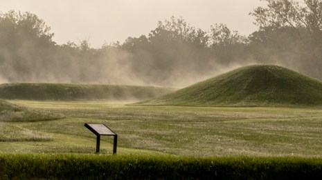 Steam fog rising from grass-covered mounds.