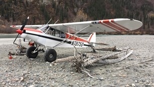 A fixed-wing aircraft with large wheels sits on a gravel beach near the water.