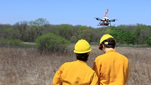 A man holds the controls for a stationary UAS while another man stand nearby.