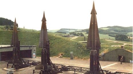 A trio of missiles stand upright and ready to fire from concrete pads
