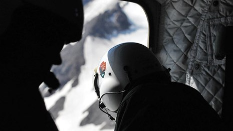 A crew member wearing a helmet peers out of a helicopter down on a mountain