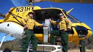 Two women stand in the door of a helicopter with a device used to ignite prescribed fires.
