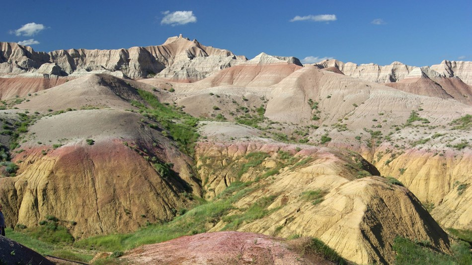 banded badlands buttes stretch far into the horizon with green prairie in valleys.