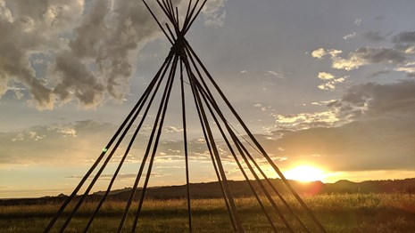 several long poles arranged in a tipi shape against a sunset and badlands buttes in background.