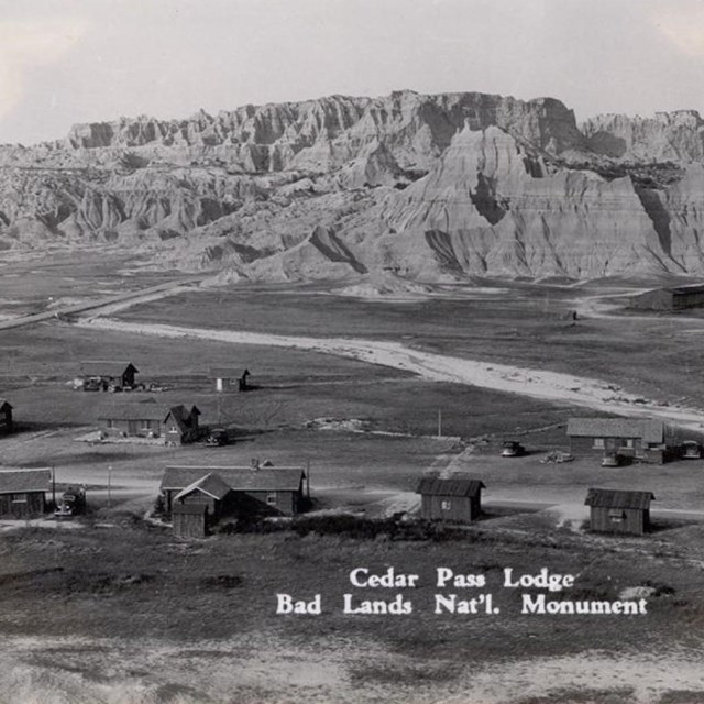 a historic black and white photo of a lodge and cabins in front of badlands buttes.