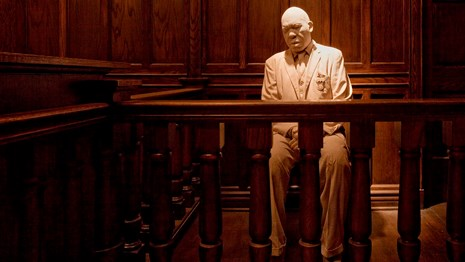 A statue of a African American man on the stand in a courtroom.