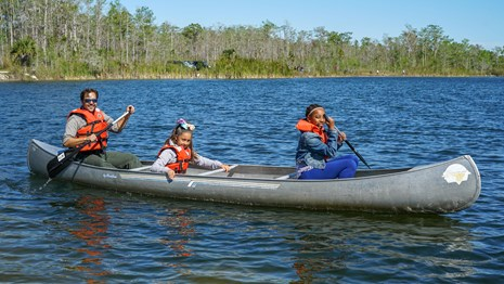 three people smile from a canoe