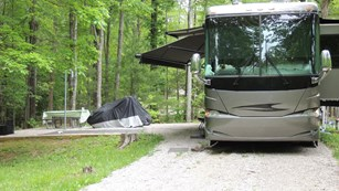 Large RV sits upon a gravel lot near a tent pad with picnic table.