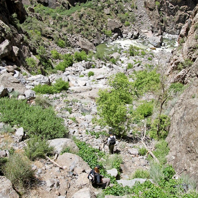 two hikers scrambling down rock ledges with the river below