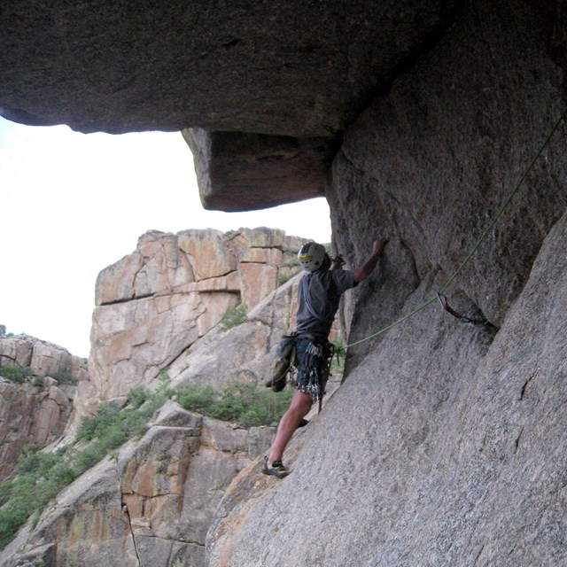 a rock climber clinging to a gray rock wall under a large overhang