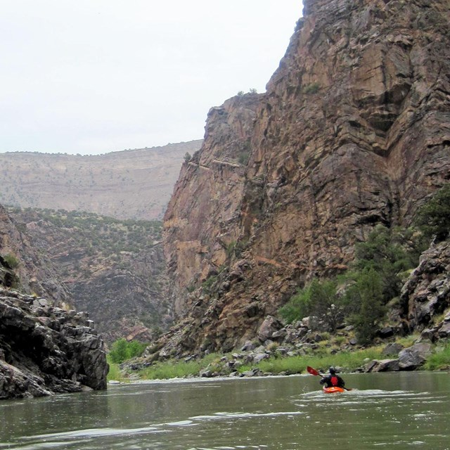 a kayaker on calm river water with dark canyon walls on either side