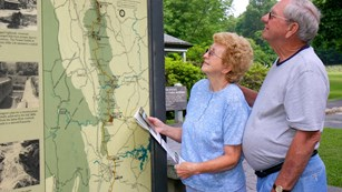 A man and women standing outdoors looking at an exhibit map