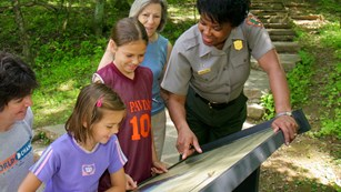 A ranger pointing out some information to four visitors on an outdoor exhibit panel
