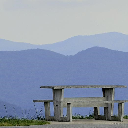 A picnic table on the edge of a grassy field, overlooking mountains.