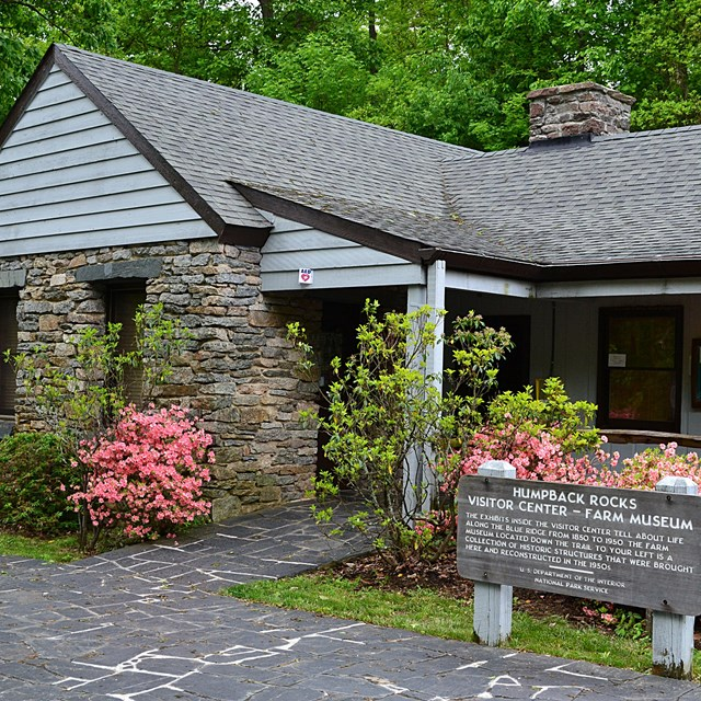 Humpback Rocks Visitor Center, a small, classic national park style building, with azaleas blooming.