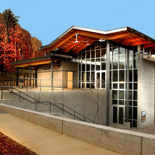 The main parkway visitor center in Asheville, with walls of windows overlooking fall color.