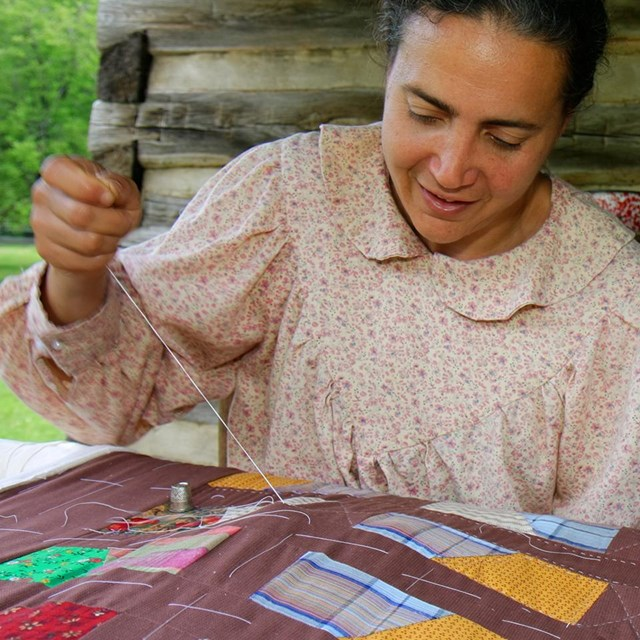 A woman in period clothing quilting on the porch of a log cabin,
