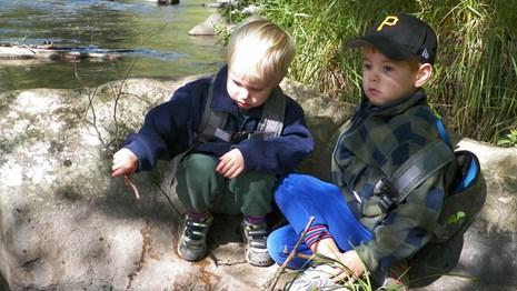 Two boys playing by the river.