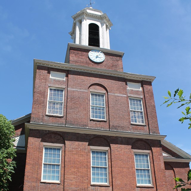 Three story brick building with white bell tower