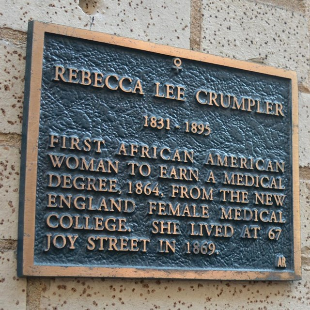 Stone wall of a building next to a black doorway. Plaque on wall about Rebecca Lee Crumpler.