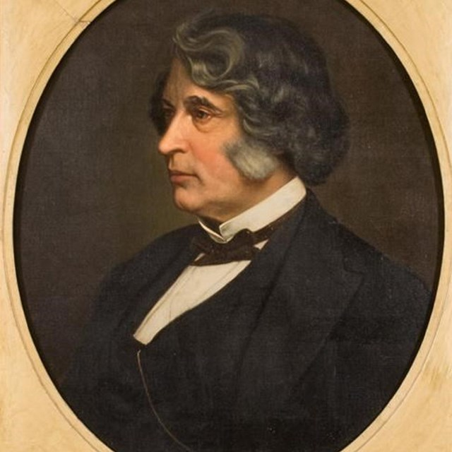 side portrait of Charles Sumner with short wavy hair tinged with gray and a dark suit.