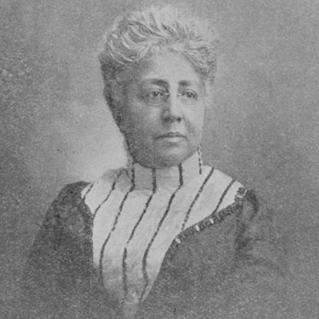 black and white print of a Black woman with short white hair, small glasses and a high-collared top