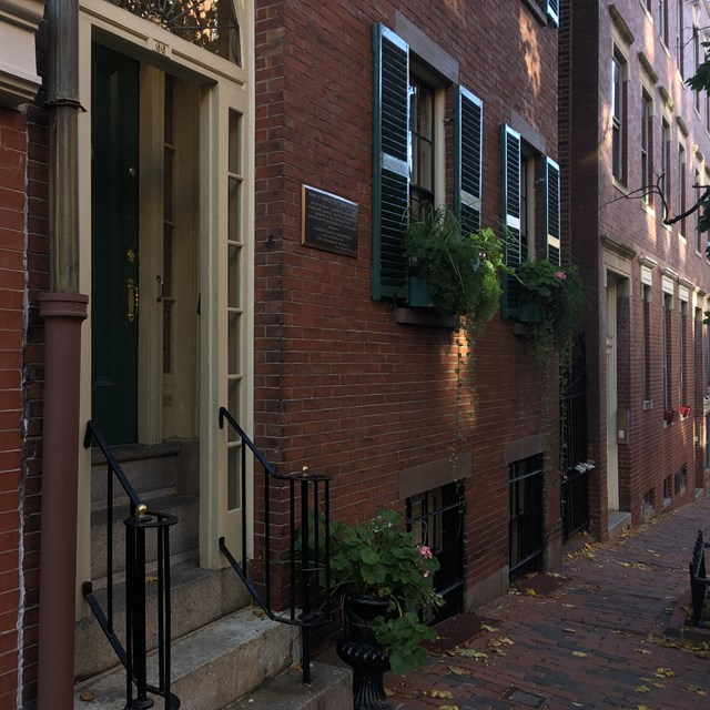 Diagonal view of shaded street of Beacon Hill with townhouses and a partial view of the sidewalk.