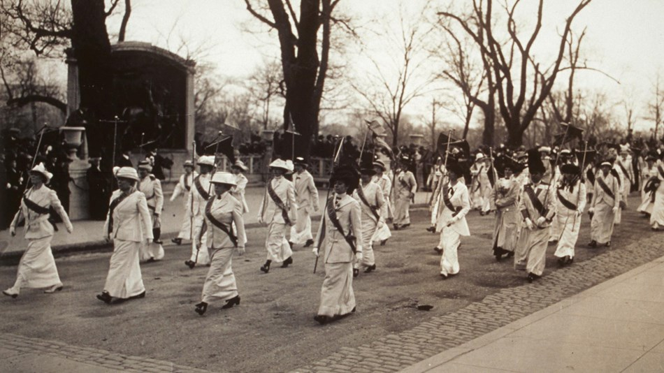 Women marching in white dresses in front of the Robert Gould Shaw 54th Memorial, Boston, MA 1914