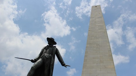 Bronze statue of William Prescott carrying a sword with Bunker Hill Monument in background
