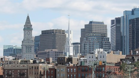 A view of Boston's skyline at daytime. White steeple of Old North in Center.