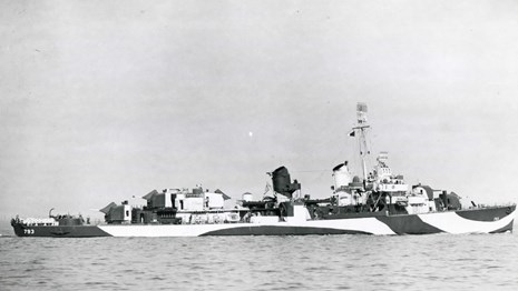 Black and white photograph of a warship in the ocean. Photo views the port broadside of the ship.