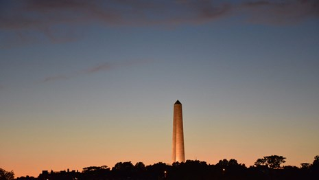 Photograph of a twilight sky with an illuminated obelisk in the center.