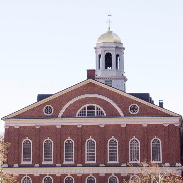 A view of brick Faneuil Hall with its white cupola with a gilt dome.