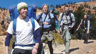 A group of four hikers with backpacks travel along a trail