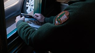 Park Ranger holds Map and Guide at Entrance Station