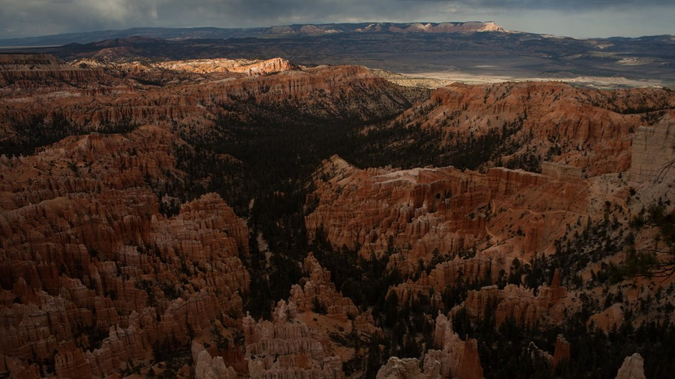 Distant view of sunlit red rocks and a distant plateau