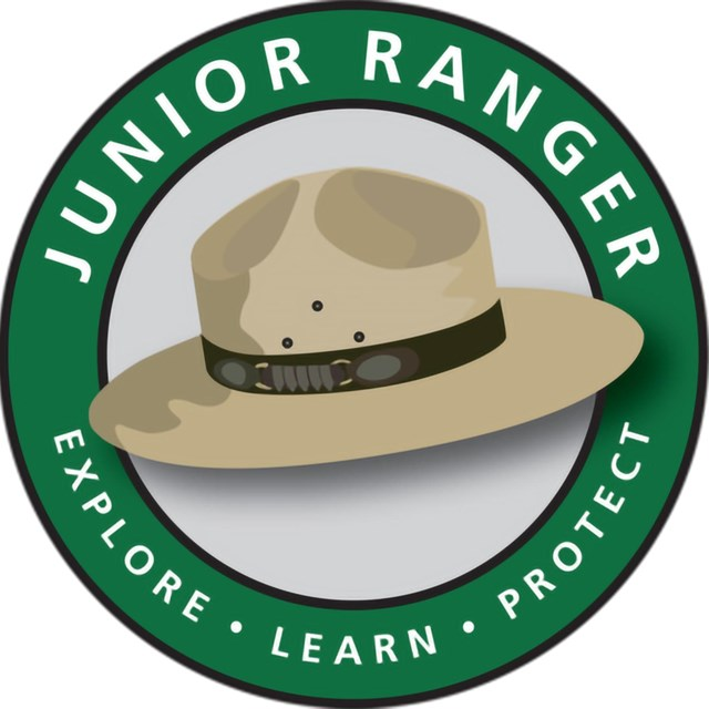 Cartoon ranger hat over green circle that reads Junior Ranger, Explore, Learn, Protect