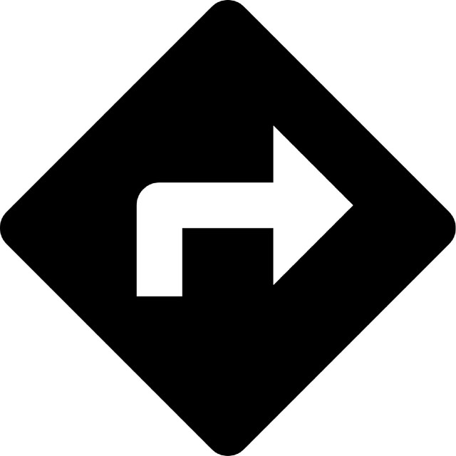 black and white right-hand arrow on road sign