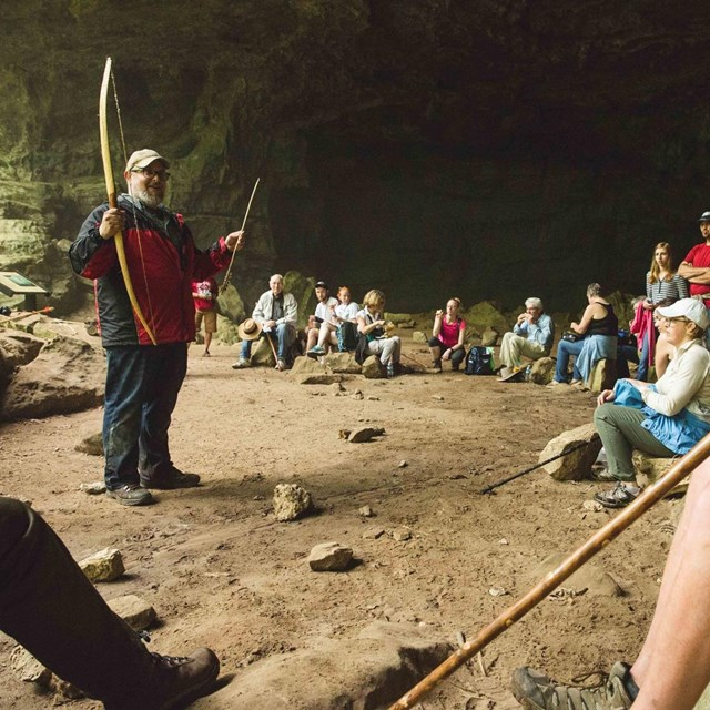 Dr. Jamie Brandon addresses a group of hikers at the Indian Rockhouse.
