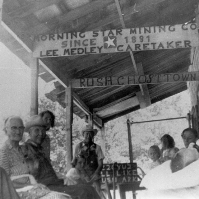Several people sit on the front porch of a building at Rush Ghost Town.