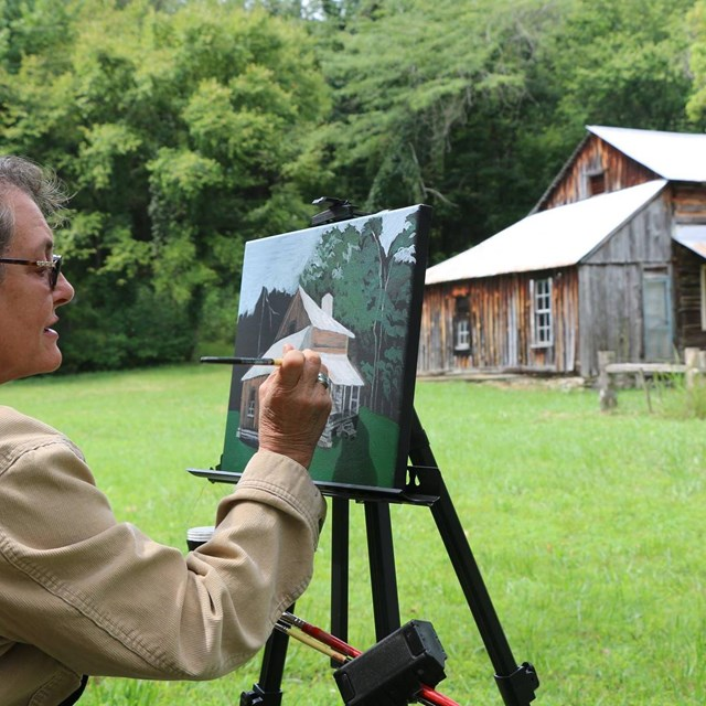 An artist paints a picture of a historic homestead that stands in the background.