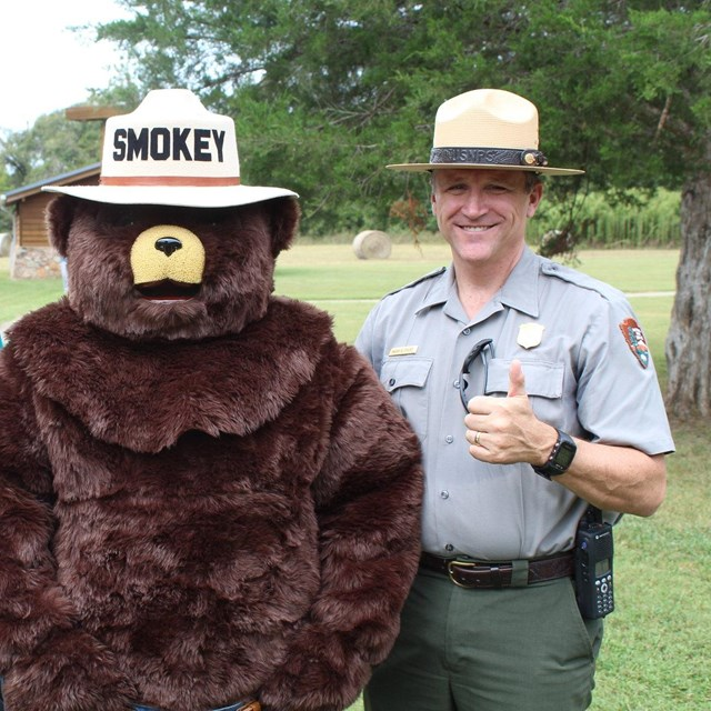 Two rangers pose with Smokey Bear.