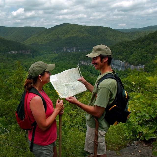 Two hikers look at a trail map while overlooking the Buffalo River.