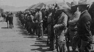 Soldiers standing next to their horses at the Presidio