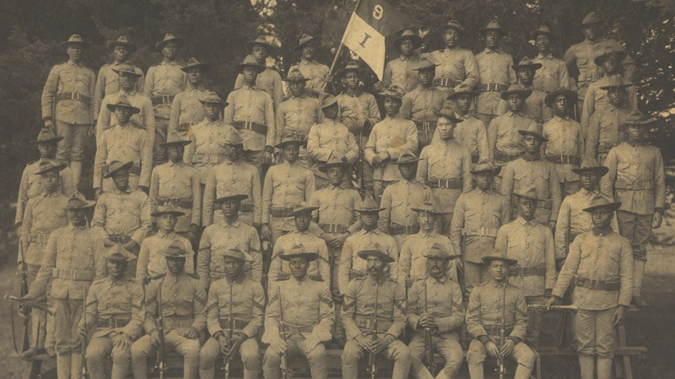 Several african american soldiers in uniforms on risers posing for a photo