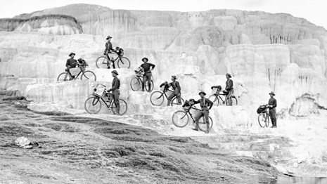 Soldiers standing next to their bikes on a natural feature in Yellowstone