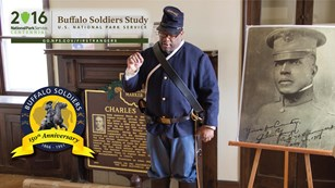 An African American ranger dressed as a Buffalo Soldier talks in front of a portrait of Chas. Young