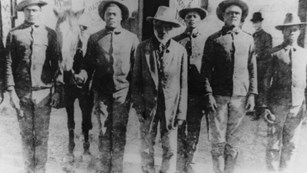 Multiple men wearing hats standing in a line