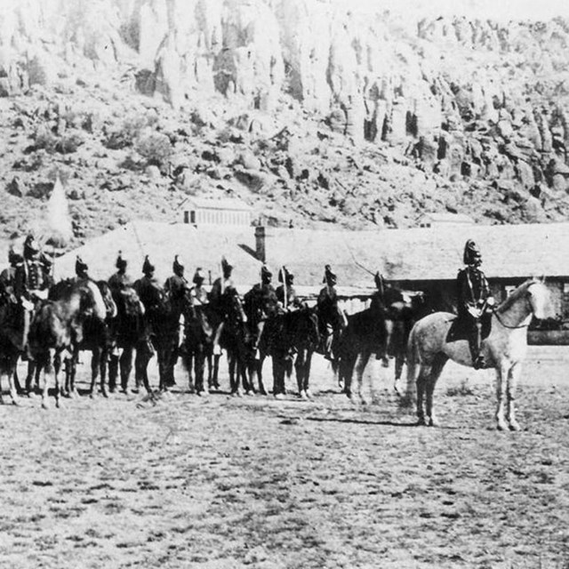 Several army soldiers on horses pose for a photo