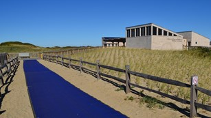 A blue mat designed for improved beach access stretches out from a grey bath house structure.